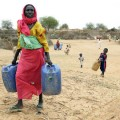 Frauen im Sudan mssen mhsam Wasser herbeischleppen. Foto: UN Photos, Olivier Chassot