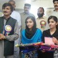 Khyber Pakhtunkhwa education minister Sardar Hussain Babak with girl students who excelled in the examinations. Credit: Ashfaq Yusufzai/IPS.