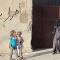 Two young girls look on as a veiled woman passes by in Aleppo, August 2014. Syrian magazine Saiedet Souria wants to provide women with the information they need to have a wider view on the world and a voice in a revolution that has largely left their views unheard. Credit: Shelly Kittleson/IPS